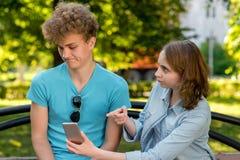 Un individuo con una muchacha en verano en un parque en naturaleza Un par joven descubre la relación La muchacha que señala en el Fotografía de archivo