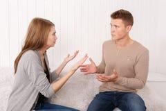 Un individuo con una muchacha está discutiendo en el sofá fotos de archivo libres de regalías
