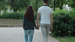 Un individuo con una muchacha que camina en el parque que lleva a cabo las manos almacen de video