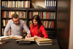 Un individuo con una muchacha que conseguía lista para el examen leyó los libros en la biblioteca foto de archivo libre de regalías