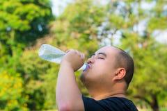 Un individuo de la cabeza calva es agua potable con sed Foto de archivo