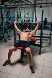 Un individuo de los deportes que hace ejercicio con un barbell grande en un fondo brillante del gimnasio Un entrenamiento del cul Imagenes de archivo