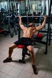 Un individuo de los deportes que hace ejercicio con un barbell grande en un fondo brillante del gimnasio Un entrenamiento del cul Fotografía de archivo libre de regalías