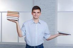 Un individuo de los jóvenes sostiene una tableta y una pila de libros en un contrapeso, haciendo las preferencias de la tableta imágenes de archivo libres de regalías