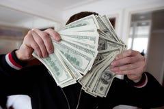 Un individuo de los ricos lleva a cabo muchos dólares delante de la cámara imagen de archivo libre de regalías