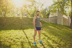 Un individuo del corredor se coloca en el parque en la puesta del sol imagen de archivo