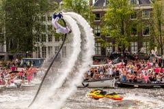 Un individuo del flyboard hace un backflip en el río de Amstel Fotos de archivo libres de regalías