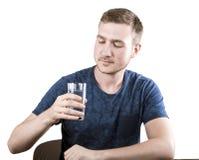 Un individuo descontento está sosteniendo un vidrio de agua en su mano, aislado en el fondo blanco El hombre enfermo está bebiend Fotografía de archivo libre de regalías