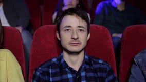 Un individuo emocional joven mira una película triste en un cine y los gritos, retrato almacen de video