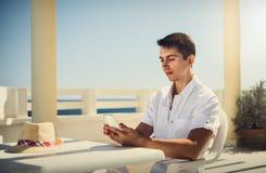 Un individuo en la ropa blanca con un teléfono Resto, viaje, vacaciones túnez Imagen de archivo
