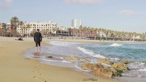 Un individuo en ropa que camina en la orilla de un mar frío y ondulado en Barcelona almacen de metraje de vídeo