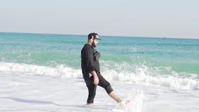 Un individuo en ropa se coloca en la orilla de un mar frío y ondulado en Barcelona almacen de video