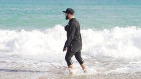 Un individuo en ropa se coloca en la orilla de un mar frío y ondulado en Barcelona metrajes