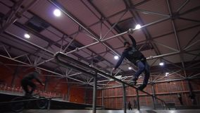 Un individuo en una camiseta negra en los rodillos realiza rutina y salta en 360, cámara lenta almacen de video
