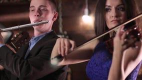 Un individuo en una chaqueta y una camisa juega la flauta, y una morenita hermosa en un vestido azul que toca el violín Repr del