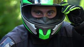 Un individuo en una motocicleta Individuo hermoso joven con su motocicleta en las montañas El individuo está mirando la cámara ci metrajes
