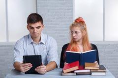 Un individuo está leyendo un eBook, y una muchacha se está sentando en una pila de diversos libros y está mirando con caridad en  Foto de archivo libre de regalías