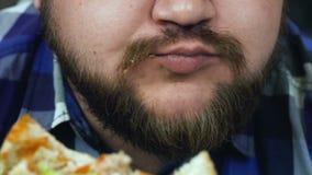 Un individuo gordo come su hamburguesa El hombre goza de la comida hecha en casa Caloría malsana de la forma de vida, frito y dañ almacen de video