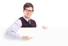 Un individuo hermoso sonriente que gesticula en un panel blanco Fotos de archivo libres de regalías