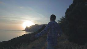 Un individuo joven con un sombrero está mirando la puesta del sol en el mar que el sol fija en el mar detrás del cabo Admira viaj metrajes