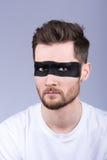 Un individuo joven con una barba y un bigote con los vidrios La tira negra en los ojos Vestido en una camiseta blanca Foto de archivo libre de regalías
