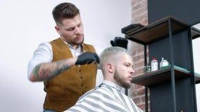 Un individuo joven consigue un corte de pelo con las tijeras del pelo con un peine almacen de video
