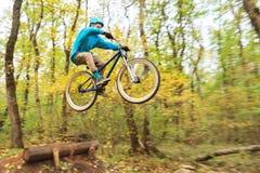 Un individuo joven en un casco vuela aterrizado en una bicicleta después de saltar de un golpeador Imagen de archivo