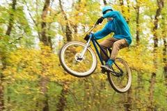 Un individuo joven en un casco vuela aterrizado en una bicicleta después de saltar de un golpeador Fotografía de archivo libre de regalías