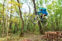 Un individuo joven en un casco vuela aterrizado en una bicicleta después de saltar de un golpeador Fotografía de archivo