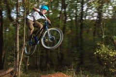 Un individuo joven en un casco vuela en una bicicleta después de saltar de un golpeador Fotografía de archivo libre de regalías