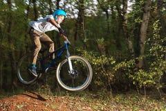 Un individuo joven en un casco vuela en una bicicleta después de saltar de un golpeador Imagen de archivo