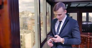 Un individuo joven en un traje se coloca cerca de la ventana en la oficina y de negociaciones sobre el teléfono, cuelga para arri almacen de video