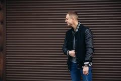 Un individuo joven en una chaqueta negra contra un fondo de las paredes rayadas oscuras que presentan y que sonríen en el fotógra Imágenes de archivo libres de regalías