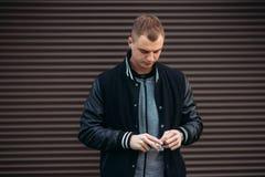 Un individuo joven en una chaqueta negra contra un fondo de las paredes rayadas oscuras que presentan y que sonríen en el fotógra Fotos de archivo libres de regalías