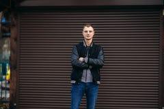 Un individuo joven en una chaqueta negra contra un fondo de las paredes rayadas oscuras que presentan y que sonríen en el fotógra Fotografía de archivo libre de regalías