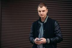 Un individuo joven en una chaqueta negra contra un fondo de paredes rayadas oscuras utiliza el teléfono Fotos de archivo