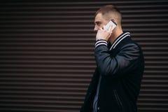 Un individuo joven en una chaqueta negra contra un fondo de paredes rayadas oscuras utiliza el teléfono Imagenes de archivo