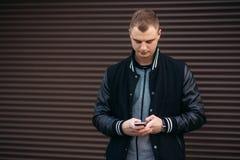 Un individuo joven en una chaqueta negra contra un fondo de paredes rayadas oscuras utiliza el teléfono Fotografía de archivo libre de regalías