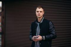 Un individuo joven en una chaqueta negra contra un fondo de paredes rayadas oscuras utiliza el teléfono Foto de archivo