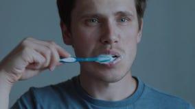 Un individuo joven est? cepillando sus dientes almacen de video