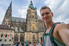 Un individuo joven, hermoso con carmesí azul hace un selfi en el fondo del St Vitus Cathedral imagen de archivo libre de regalías