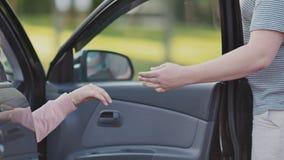 Un individuo joven invita a su novia para un paseo y abre la puerta de su coche Él da su mano Verano reconstrucción almacen de video