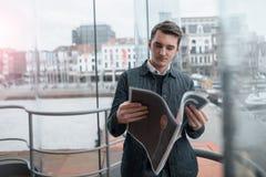 Un individuo joven lee un periódico dentro Foto de archivo libre de regalías