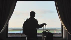 Un individuo joven mira el avión que saca de la ventana de su habitación y de las hojas con una maleta para subir metrajes