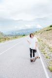 Un individuo joven - patinador que se coloca antes de una raza en una carretera nacional imagen de archivo libre de regalías