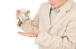Un individuo joven que intenta extraer el dinero de un envase de cristal Foto de archivo