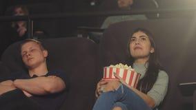 Un individuo joven se cayó dormido en un cine mientras que miraba una película, mientras que su muchacha continúa entusiasta mira metrajes