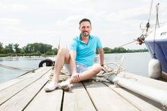 Un individuo joven se sienta en polo azul en el embarcadero cerca del yate hombre hermoso turístico sonreído feliz que relaja y q fotografía de archivo