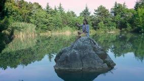 Un individuo joven se sienta en una piedra en el medio del lago, toma un selfie Utiliza un smartphone para la fotografía r almacen de video