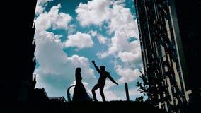 Un individuo joven y un baile de la muchacha contra un cielo hermoso nubes imponentes en el fondo dos amantes que hacen girar en  almacen de metraje de vídeo